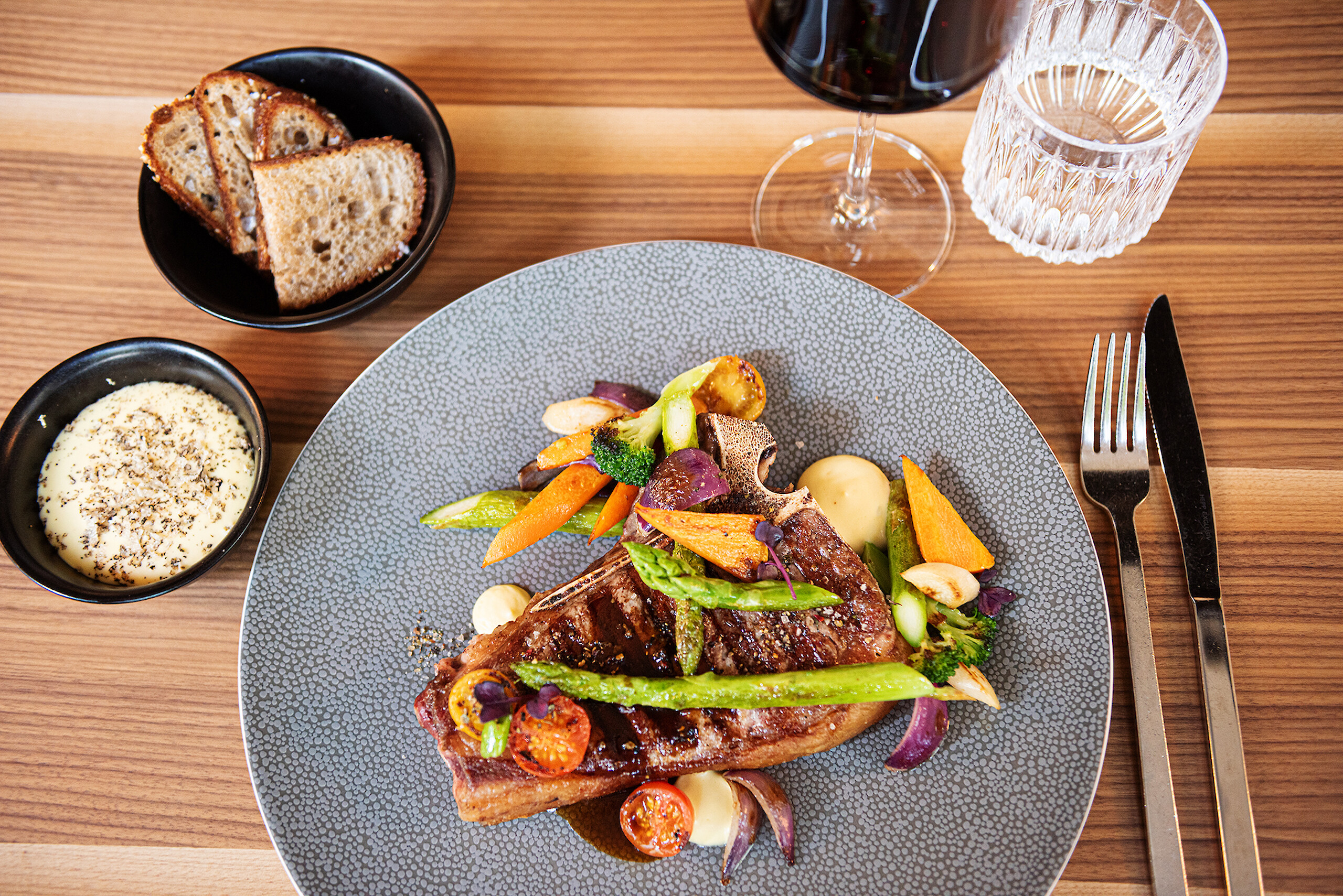 A freshly prepared Côte de Boeuf with vegetable garnish and delicious red wine