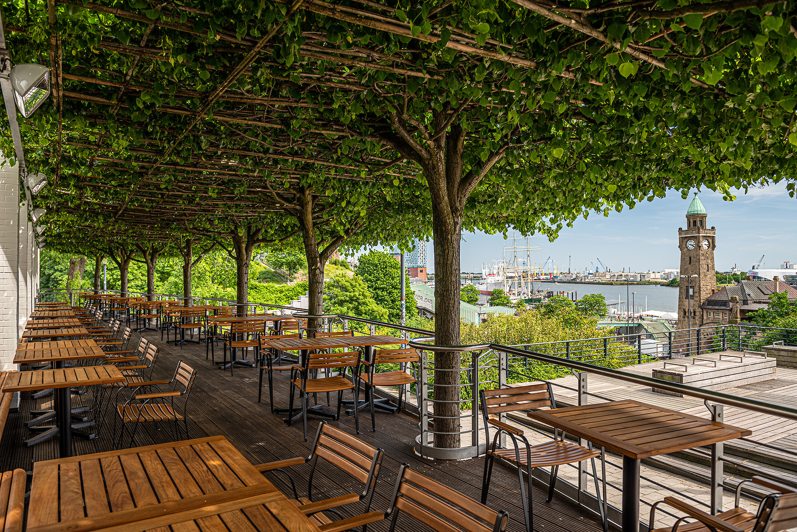 The treetop-covered terrace of the Port Restaurant with a view across the harbor