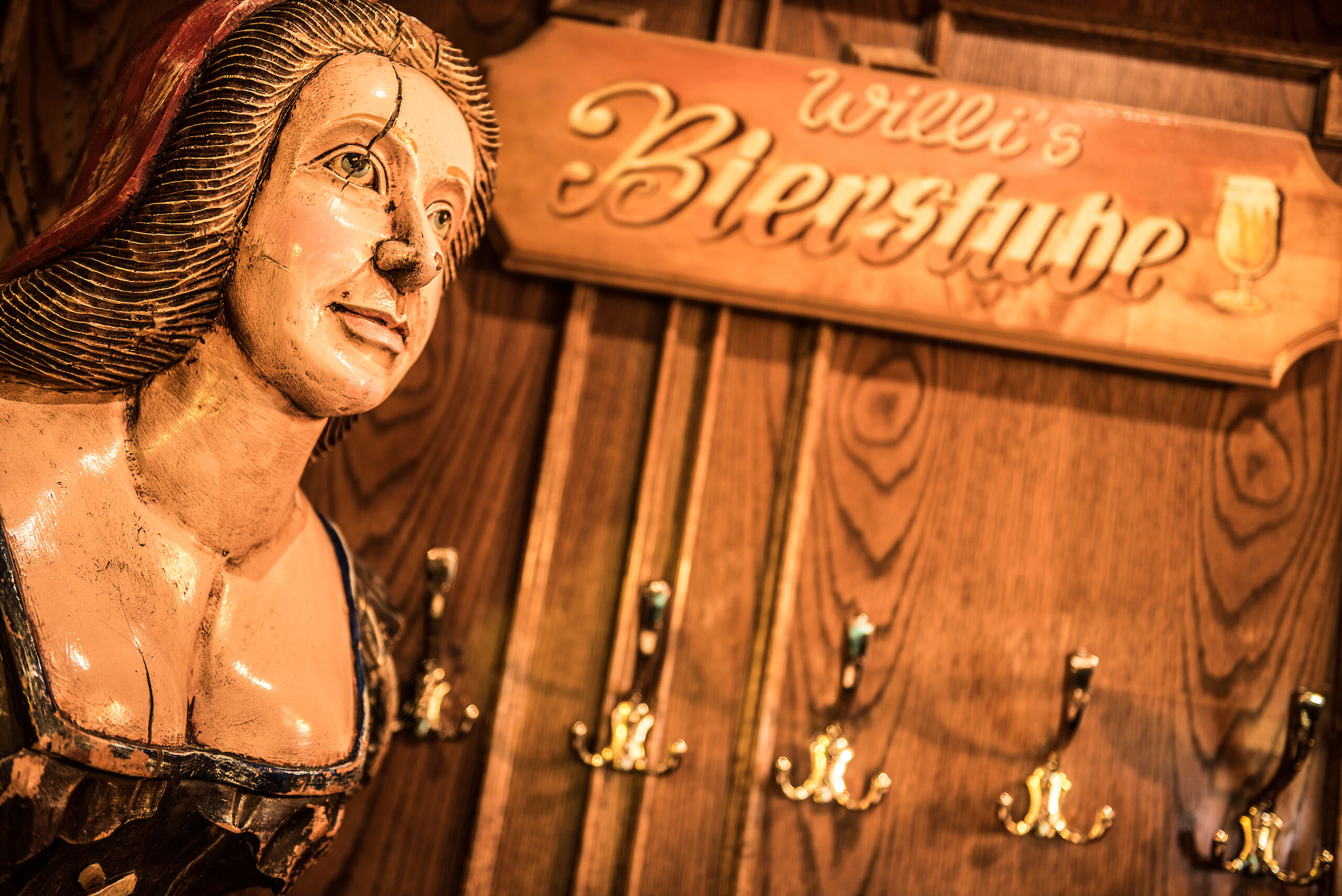 A wooden board engraved with WILLI'S Bierstube with a female figurehead