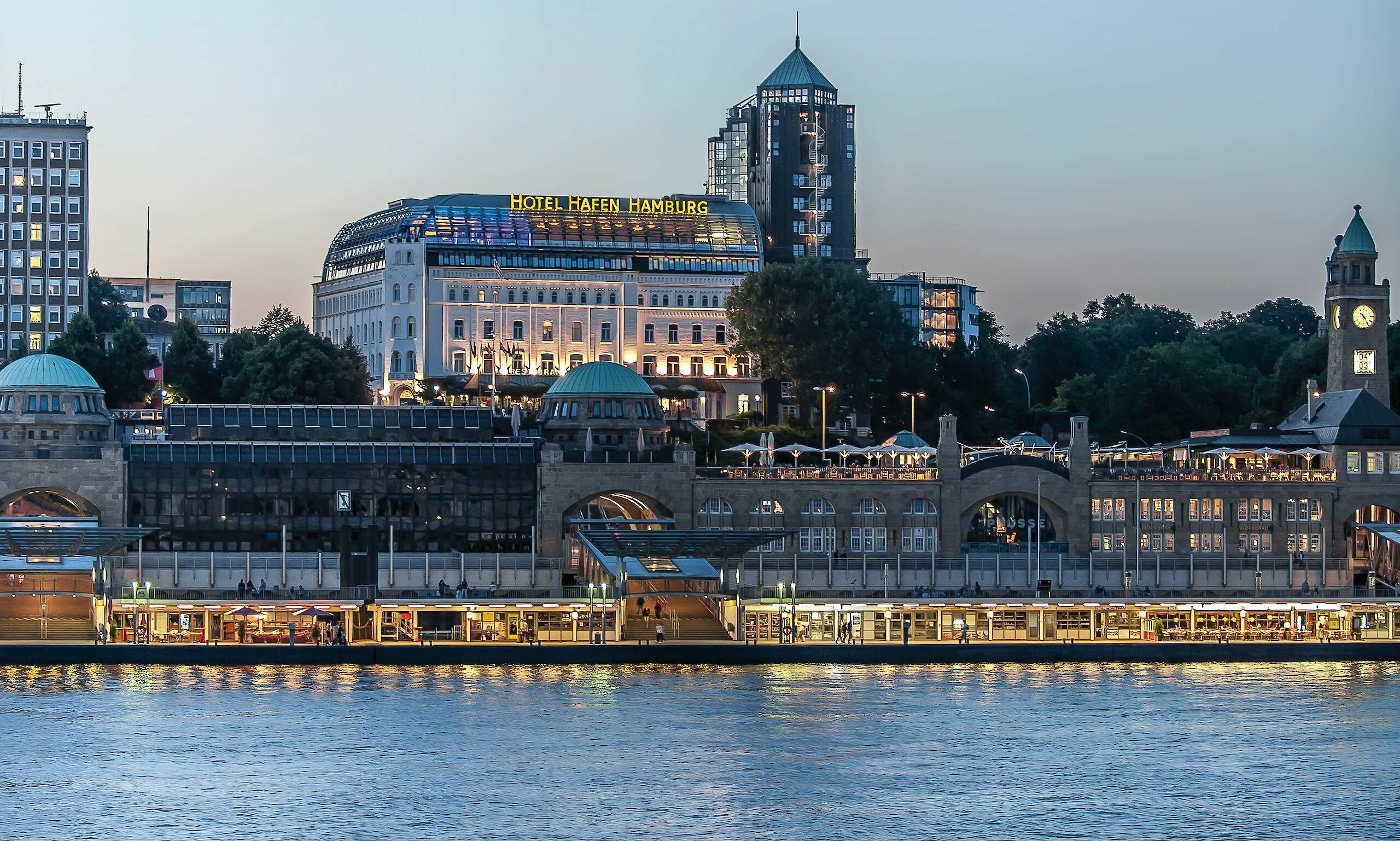 The exterior of the Hotel Hafen Hamburg in the glow of the evening lights