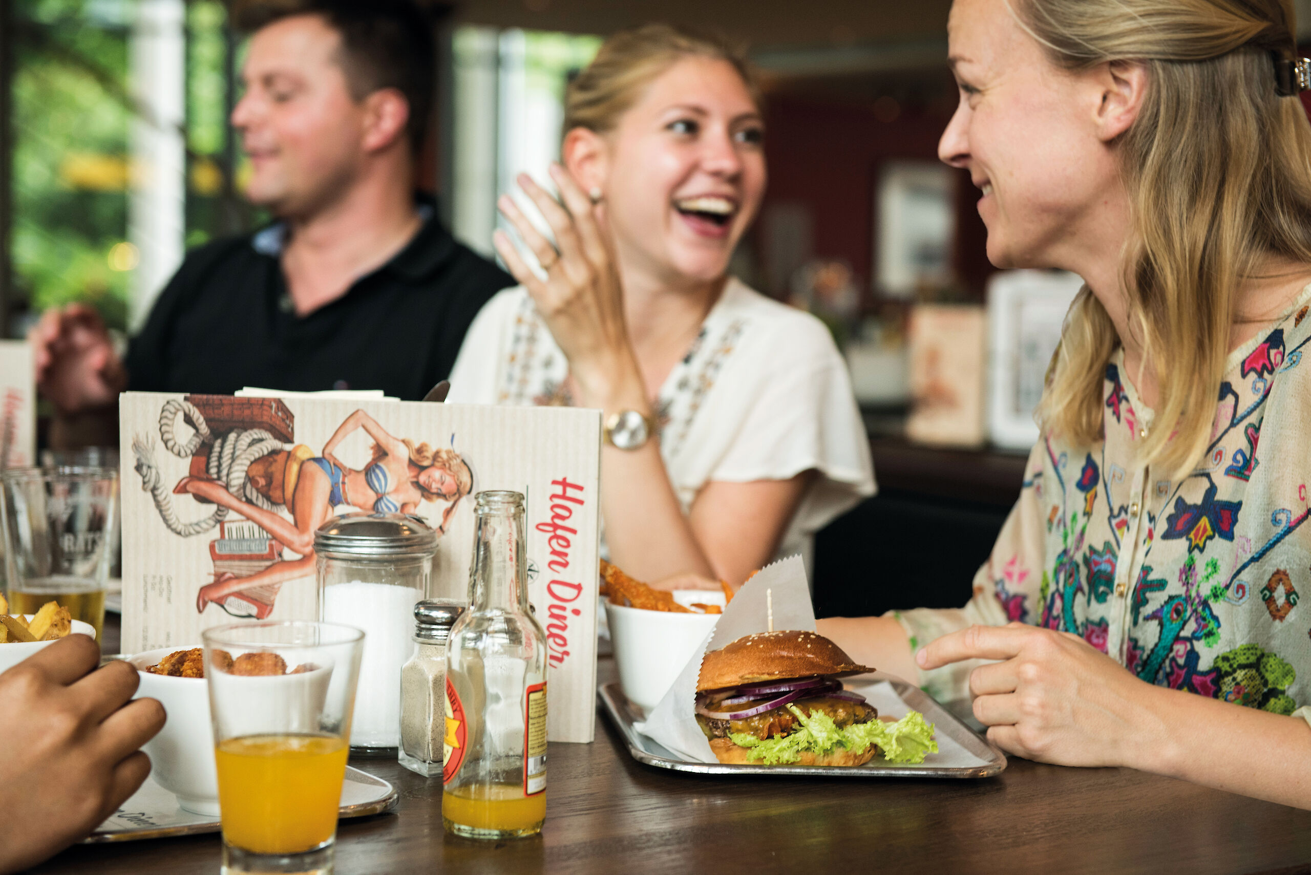 Guests enjoying their day with a juicy burger at the Hafen Diner