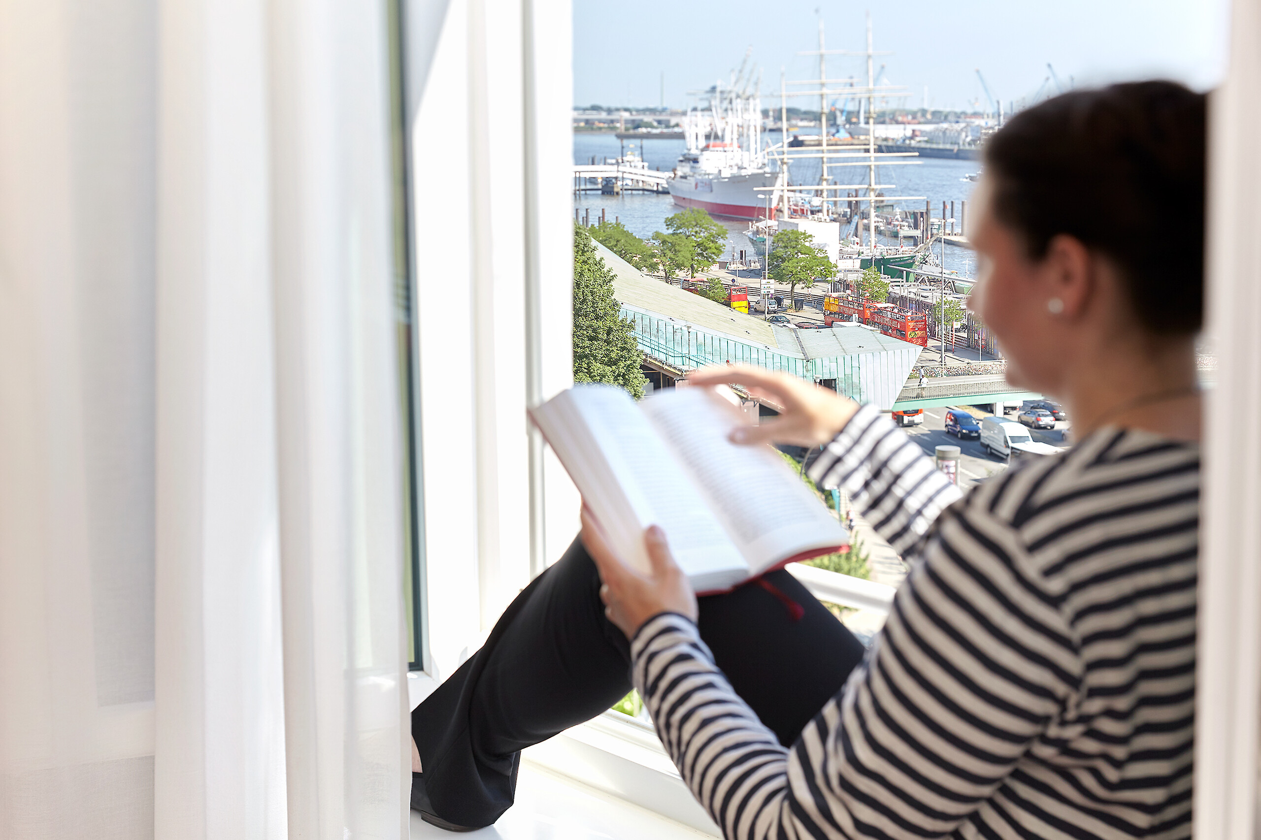 A guest reading a book with a beautiful view of the harbor