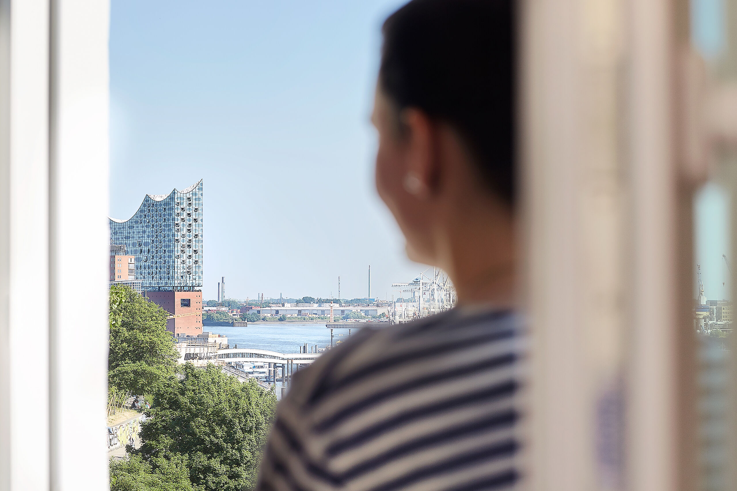 A guest enjoying the view of the Elbphilharmonie from his hotel room