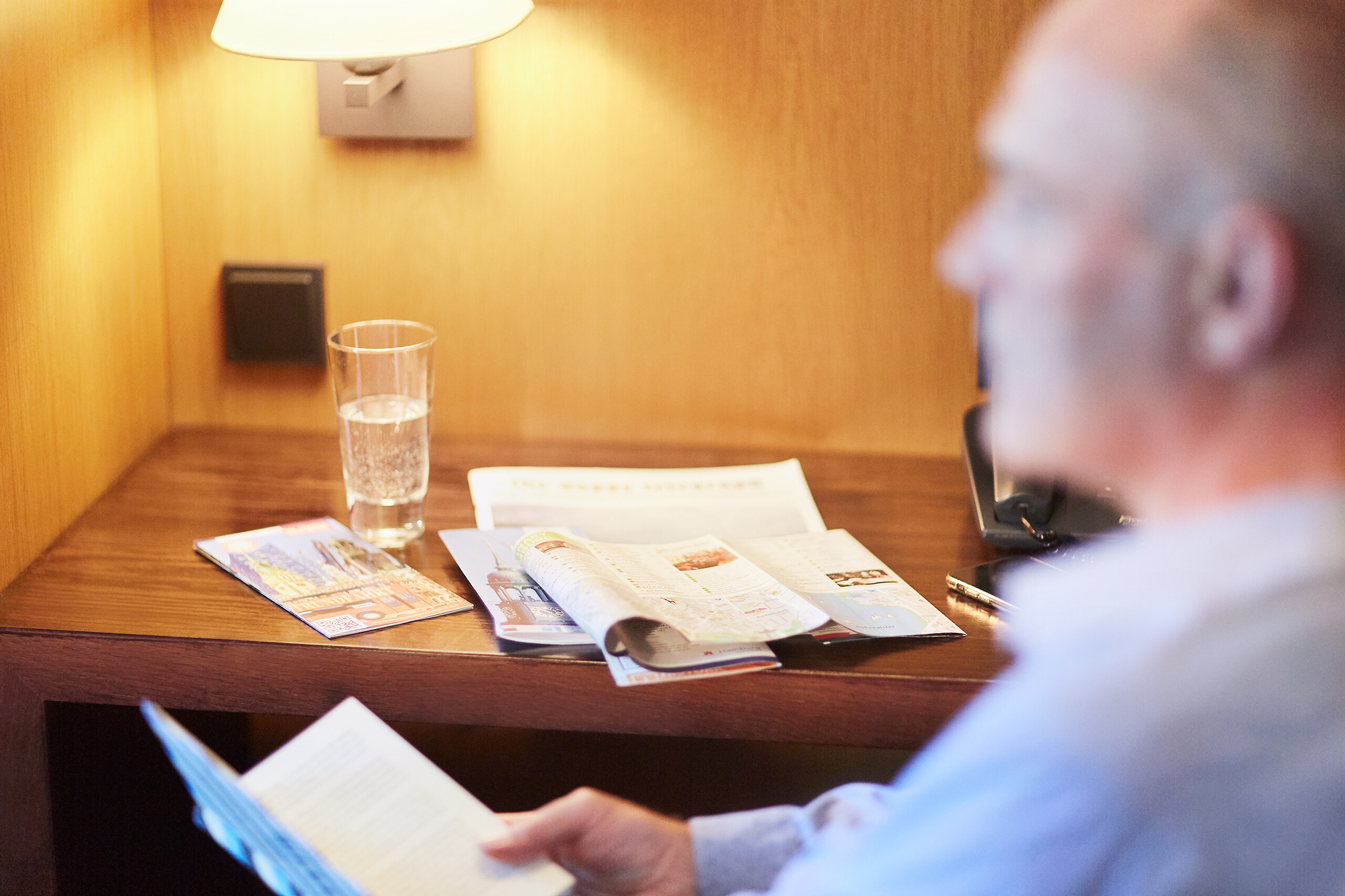 A hotel guest reading brochures at his desk in his lieutenant hotel room